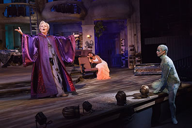 Production photo of Prospera speaking, Mirnada sleeping, and Ariel leaning on the stage listening