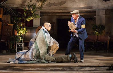 Production photo of Caliban wearin gaberdine sitting on top of Trinculo as Stephano holds before him a bottle.