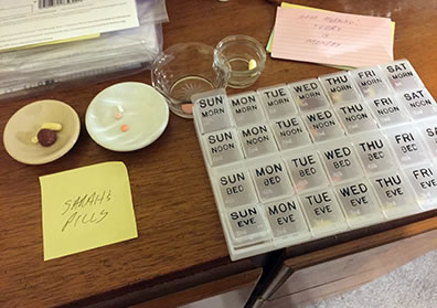 "A pill organizer on a dresser top, with small dishes adjacent to it each containing pills, and a ""Sarah's Pills"" yellow Post-it note,"