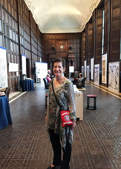 "Sarah, gorgeous as ever, stands in the middle of the Folger's Great Hall. Her ""brain"" is a red Washington Nationals purse hanging over her shoulder down to her waist."