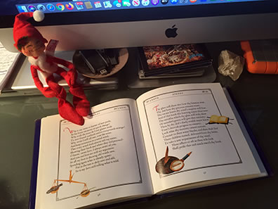 The illustrated book of Shakespeare sonnets opened to Sonnet 77, with an Anna Lee elf sitting on it, the bottom edge of desktop iMac in the background.