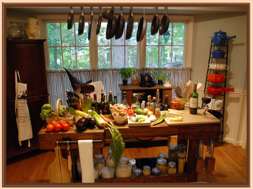 Photo of kitchen with prep table covered in vegetables, cheese, Talbot wine, and a witch's hat in the background